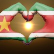 Heart and love gesture by hands colored in suriname flag during — Stock Photo #9902560