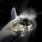 Golden wedding rings and smoke — Stock Photo