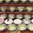Stock Photo: Small bowls with water and rice around a temple