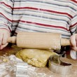 Child rolling dough on wooden desk — Stock Photo