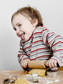 Happy young child with rolling pin in grey background — Stock Photo