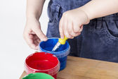 Child holding brush in paint tub — Stock Photo