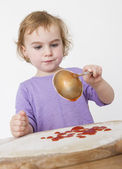 Child putting sieved tomatoes on dough — Stockfoto