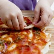 Small hands preparing pizza — Stock Photo #36227753