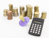 Pacifier with hard money and pocket calculator — Stock Photo