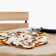 Pizza with cutter on small desk — Stock Photo