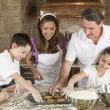 Attractive Family Baking and Eating Cookies In A Kitchen — Stock Photo