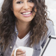 Woman Smiling Drinking Tea or Coffee Using Tablet Computer - Stock Photo