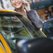 Young Woman Talking on Cell Phone By Yellow Taxi — ストック写真
