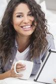 Donna sorridente bere tè o caffè utilizzando computer tablet — Foto Stock
