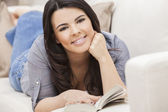 Happy Hispanic Woman Reading Paperback Book at Home — Stock Photo