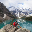 Foto Stock: Hiking Man Looking at Moraine Lake & Rocky Mountains