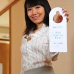 Asian woman holding up hotel signage — Stock Photo #6539309