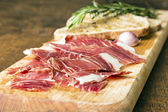 Spanish ham with toasts as background — Stock Photo
