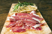 Spanish ham with toasts and rosemary — Stock Photo
