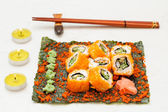 Set of sushi roll on nori with chopstick and candle — Stock Photo