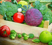 Fresh fruits and vegetables in a creates — Stock Photo