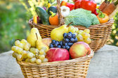 Organic fruits in wicker basket — Stock Photo