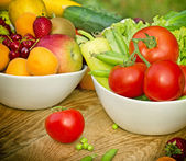 Organic fruits and vegetables in a bowls — Stock Photo