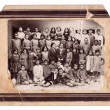 Old and damaged school photo c.1920 in old paper frame — Stock Photo #24246845