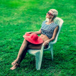 Fashion girl sitting resting on a chair in the park — Stock Photo