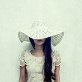 Fashion portrait of a sensual girl in a hat against the wall — Stock Photo