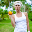Portrait of a young athletic girl with orange — Stock Photo