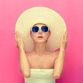Porträtt av en flicka i en hatt på en rosa bakgrund — Stockfoto