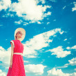 Portrait of retro girl on the blue sky background — Stock Photo