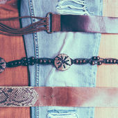 Vintage belts and jeans on wooden background — Foto de Stock