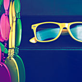 Glasses and brightly colored beads on black grungy background — Stock Photo