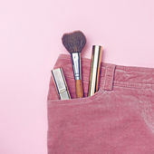 Small set of make-up in pink pants pocket — Stock Photo