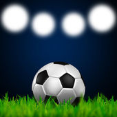 Football in the green grass on spotlight background — Stock Photo