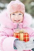 Child holding Christmas gift — Stock Photo