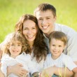 Happy family in spring field — Stock Photo #21384599