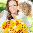 Child and woman with bouquet of flowers - Stock Photo