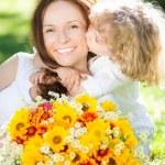 kind en vrouw met boeket van bloemen — Stockfoto