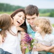 Happy family in spring field - Stock Photo