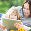 Stock Photo: Family using tablet PC outdoors