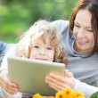 Family using tablet PC outdoors — Stock Photo