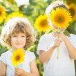 Happy children playing with sunflowers — Stock Photo