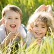 Happy children lying on grass — Stock Photo