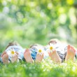 Kids with daisy flowers on green grass — Stock Photo #21384947