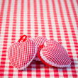 Three hearts on gingham tablecloth — Stock Photo