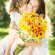 Woman and child holding bouquet of flowers - Stockfoto