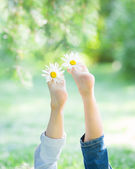 Childrens feet with flowers — Stock Photo