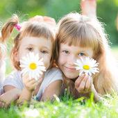 Happy children with flowers — Stock Photo