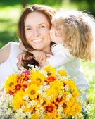 Child and woman with bouquet of flowers — Стоковое фото