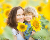 Womn and child in sunflower field — Stock Photo