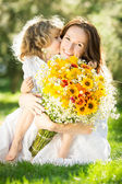 Woman and child holding bouquet of flowers — Stok fotoğraf